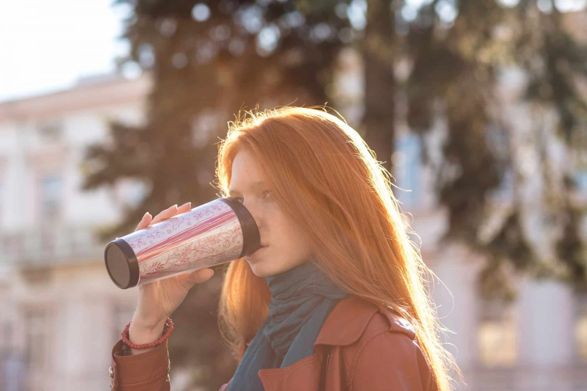 Beautiful redhead lady drinking coffee from tumbler