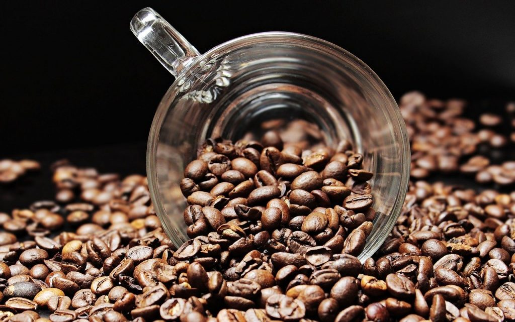 coffee beans pouring out of cup